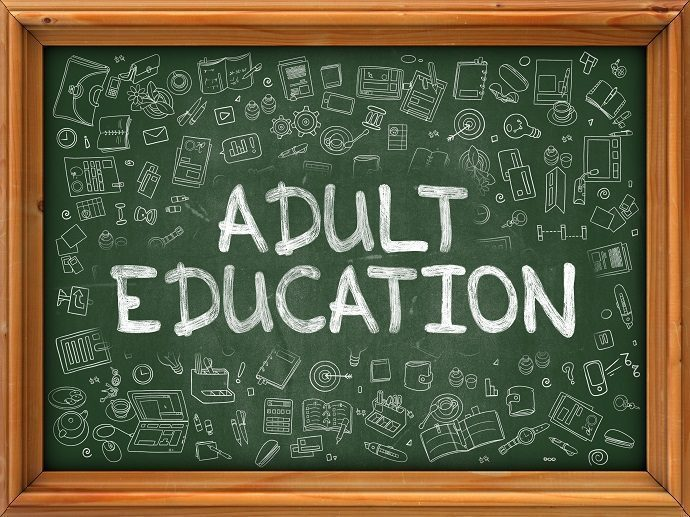 "A green chalk board that has ""Adult Education"" written in white chalk"
