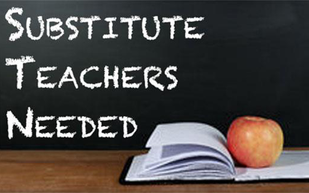 "A black chalk board with ""Substitute Teachers Needed"" written in white chalk. There is an open book and an apple on a wood desk underneath it."